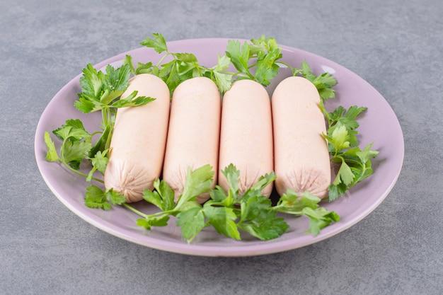 Fioletowy talerz gotowanych kiełbasek z pietruszką.