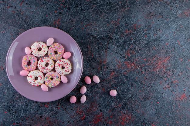 Fioletowy talerz kolorowych pączków na ciemnej powierzchni.