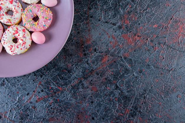 Fioletowy talerz kolorowych pysznych pączków na ciemnej powierzchni.