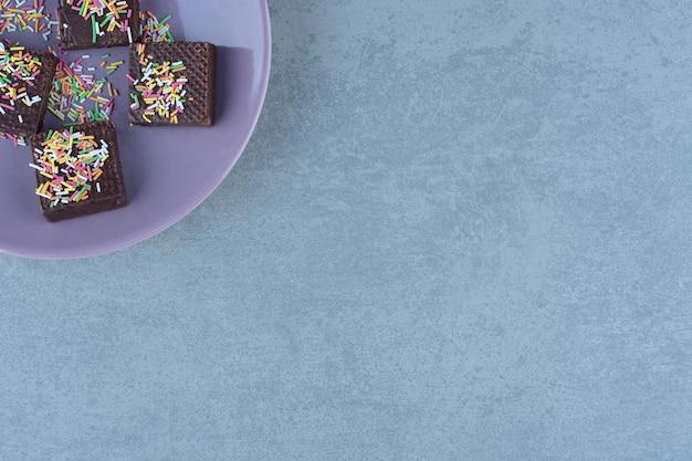 Fioletowy talerz na rogu. wafelki czekoladowe z posypką na talerzu.