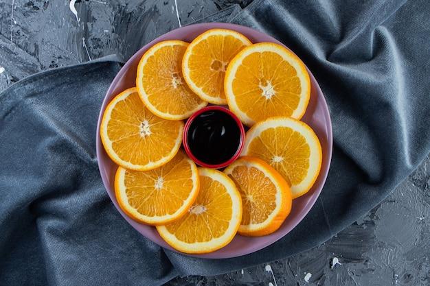 Fioletowy talerz pokrojony w plasterki soczystych pomarańczy na powierzchni marmuru.