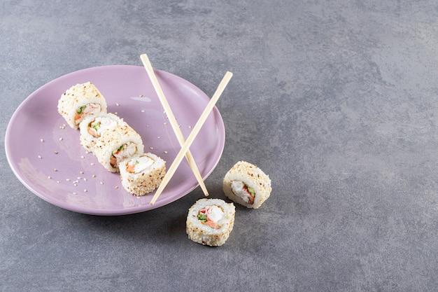 Fioletowy talerz rolek sushi z sezamem na tle kamienia.