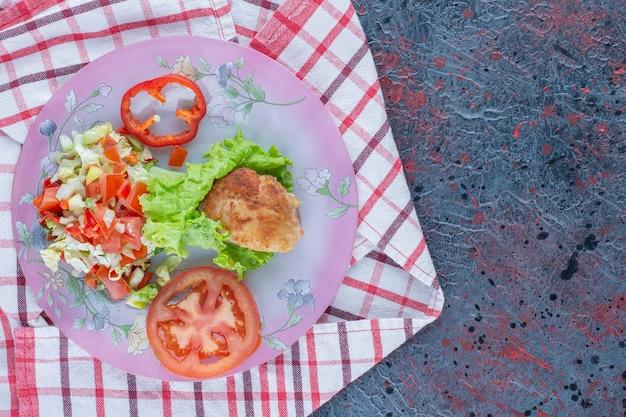 Fioletowy talerz sałatki warzywnej i mięsa z kurczaka.