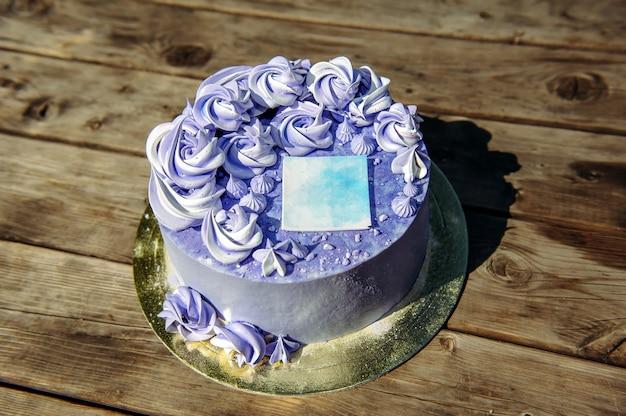 Fioletowy tort urodzinowy z kremowymi kwiatami i ozdobną naklejką na drewniane tła