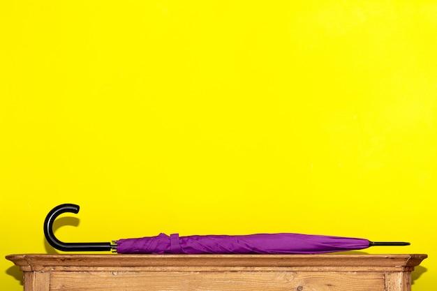 Fioletowy złożony parasol leży na drewnianej komodzie na żółtej ścianie. koncepcja wnętrza, porządek w domu.