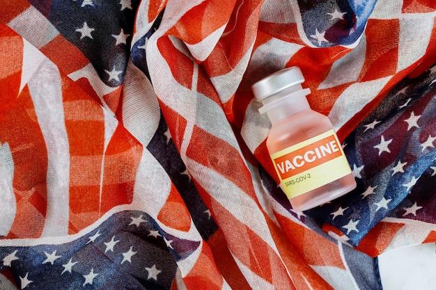 Fiolki szklane pojemniki z amerykańską szczepionką sars-cov-2, koronawirusem covid-19 z flagą usa