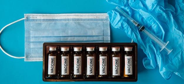 Fiolki ze szczepionką, strzykawką, rękawiczkami i maską na niebieskim tle, z bliska. szczepienie koronawirusem covid-19 i poprawa odporności.