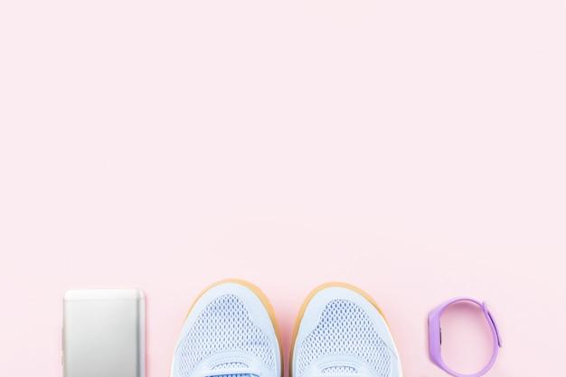 Fiołkowe żeńskie trampki, monitor fitness i smartphone na różowym tle. leżał płasko, kopia przestrzeń.