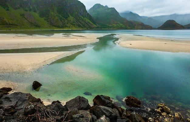 Fiordy i jeziora lofotów pochmurny krajobraz z piaszczystą plażą, jeziorem i górami. wgląd nocy polarny dzień lato.