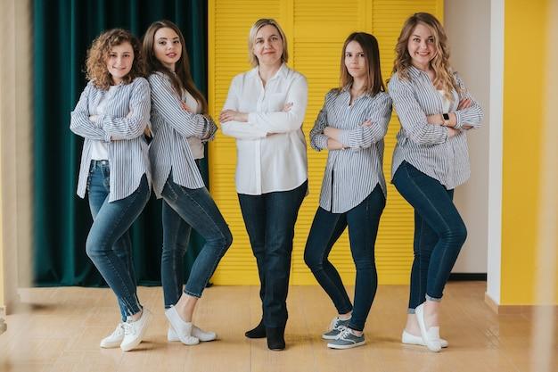 Firma dziewcząt pozujących stojących na żółtym tle.