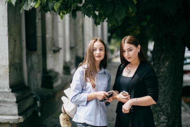 Firma młodych przyjaciół z smartfonów spacerujących w mieście