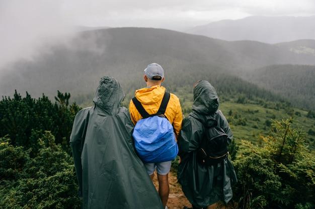 Firma podróżników w płaszczach przeciwdeszczowych stoi na szczycie góry. przyjaciele cieszy się natura widok w deszczowym mgłowym dniu