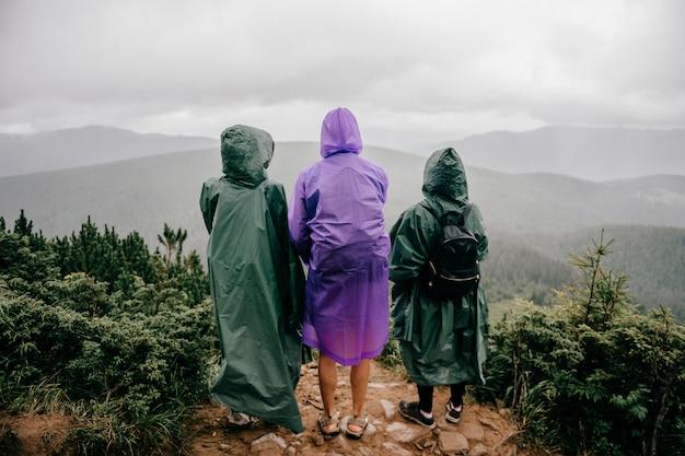 Firma podróżników w płaszczach przeciwdeszczowych stoi na szczycie góry. przyjaciele cieszy się natura widok w dżdżystym mgłowym letnim dniu.
