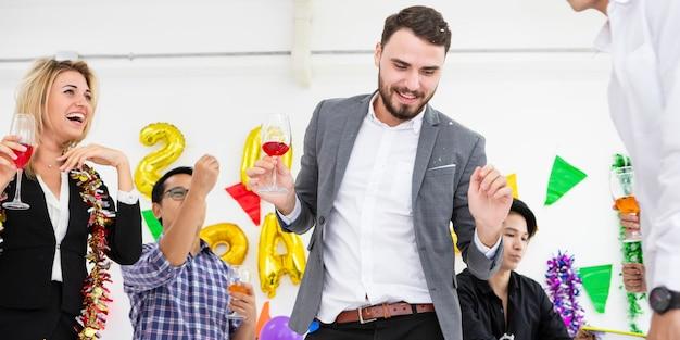 Firma przyjaciół trzyma flety szampana podczas gdy tanczący przy przyjęciem w białym pokoju.