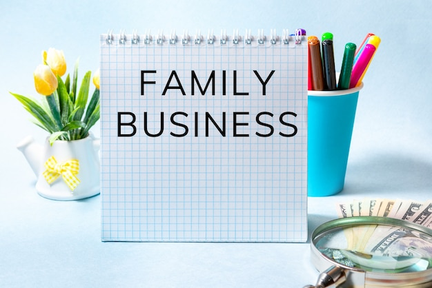 Firma rodzinna, tekst na białej kartce. niebieskie tło z banknotów papeterii i us. pomysł na biznes.