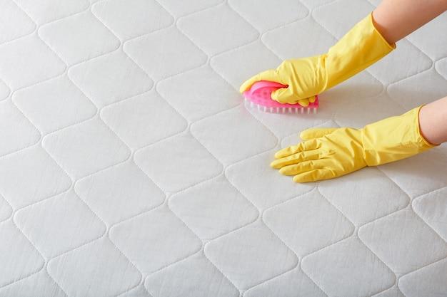 Firma sprzątająca pracownik czyści ręcznie powierzchnię materaca na łóżku za pomocą szczotki. czyszczenie powierzchni dezynfekcyjnych. ręka w rękawiczce do chemicznego czyszczenia materaca. miejsce na kopię.