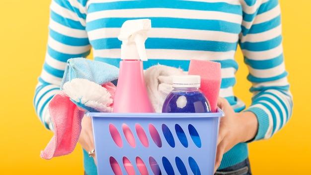Firma sprzątająca. profesjonalne sprzątanie domu. kobieta z koszem zaopatrzenia.