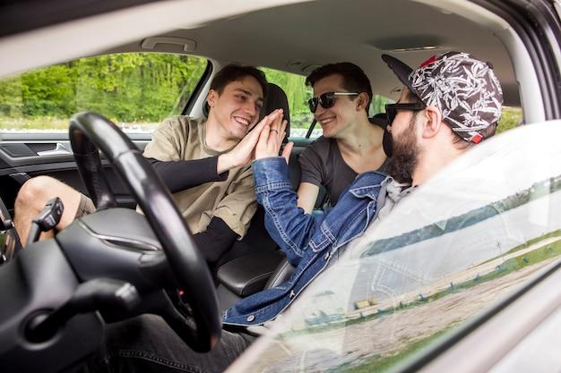 Firma szczęśliwych przyjaciół wita się w samochodzie