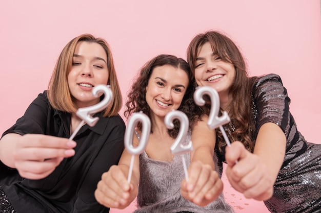 Firma wesołych dziewczyn na różowym tle trzyma numery 2022, obchody nowego roku, przyjęcie bożonarodzeniowe.