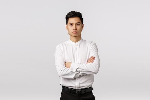 Firmowa promocja, rekrutacja i koncepcja biznesowa. atrakcyjny, pewny siebie azjatycki przedsiębiorca, krzyżujący ramiona na piersi, skupiony na kamerze i pewny siebie, zdolny poradzić sobie z każdym zadaniem, rozwiązać problemy