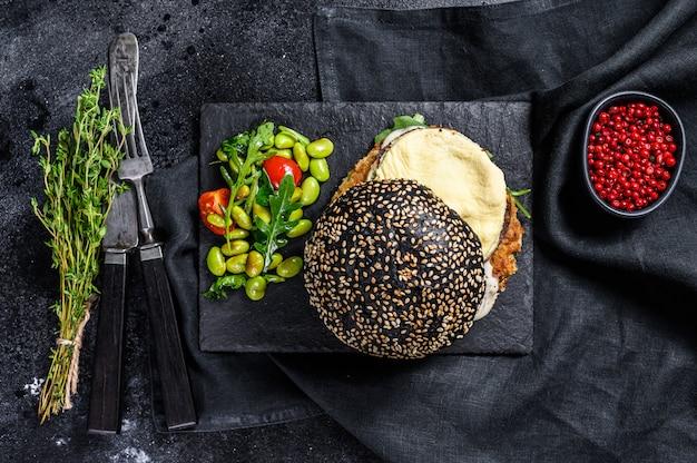 Fishburger z czarną bułką brioche, omletem, kotletem rybnym i rukolą. widok z góry