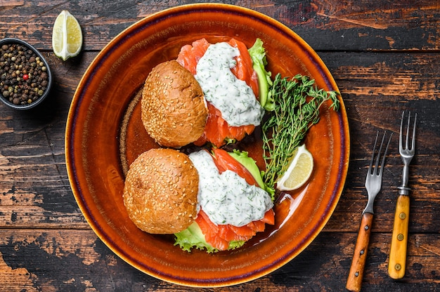 Fishburger z solonym łososiem rybnym, awokado, bułką burgerową, sosem musztardowym i sałatką lodową. ciemny drewniany stół. widok z góry.