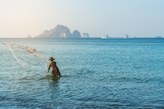 Fisher mężczyzna połowów w okolicy plaży morza