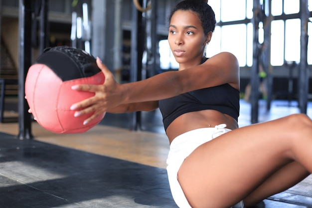 Fit i muskularna kobieta ćwiczenia z piłką lekarską na siłowni.