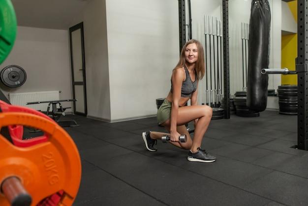 Fit kobieta ćwiczy rzuca z hantlami na siłowni. koncepcja zdrowego stylu życia