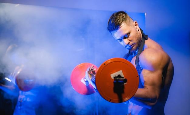 Fit młody człowiek podnoszenia sztangi robi trening na siłowni. sport, fitness, podnoszenie ciężarów, kulturystyka, trening, sportowiec, koncepcja ćwiczeń treningowych. widok z boku.