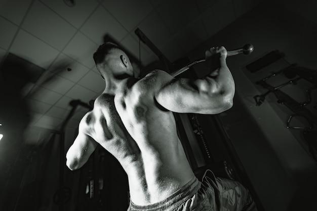 Fit młody człowiek robi trening na siłowni. sport, fitness, podnoszenie ciężarów, kulturystyka, trening, sportowiec, koncepcja ćwiczeń treningowych. widok z tyłu.