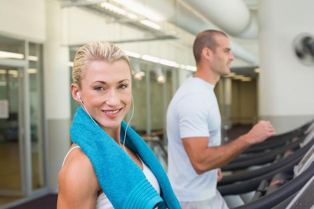 Fit młodych para działa na bieżni w siłowni