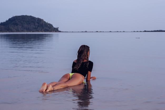 Fit opalona młoda kobieta kaukaska w morzu o zachodzie słońca
