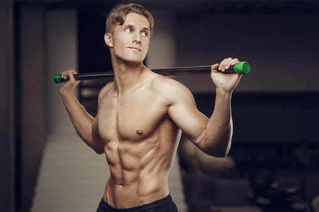Fitness człowiek na treningu w siłowni z mięśni rozciągających bodybar