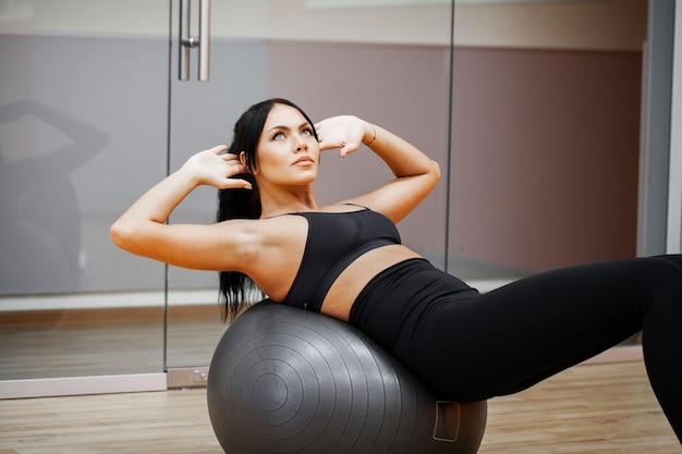 Fitness girl. seksowna sportowa dziewczyna pracuje w gym. fitness kobieta robi ćwiczenia