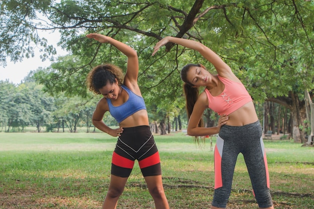 Fitness kobiet praktykujących jogę w parku. kobiety robią trening fitness w parku.