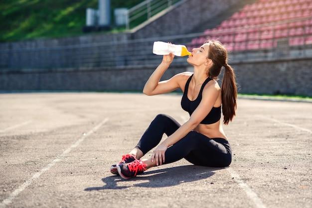 Fitness kobieta lekkoatletka wody pitnej lub napój energetyczny butelki sportu