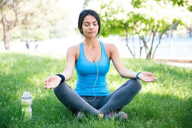Fitness kobieta medytuje na zielonej trawie
