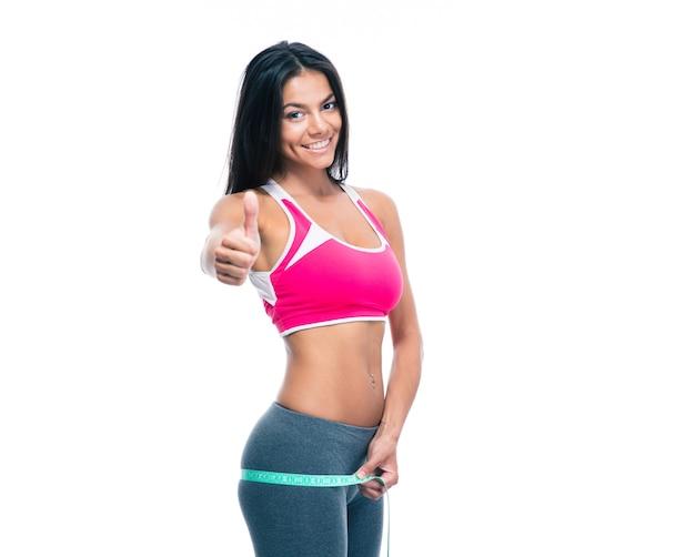 Fitness kobieta mierzy jej pośladki taśmą mierniczą
