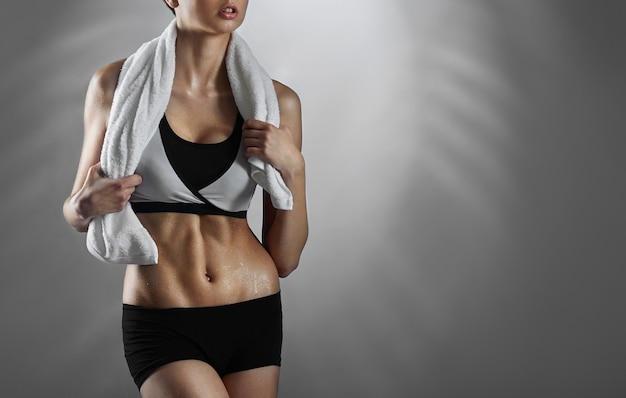 Fitness kobieta pozuje z ręcznikiem