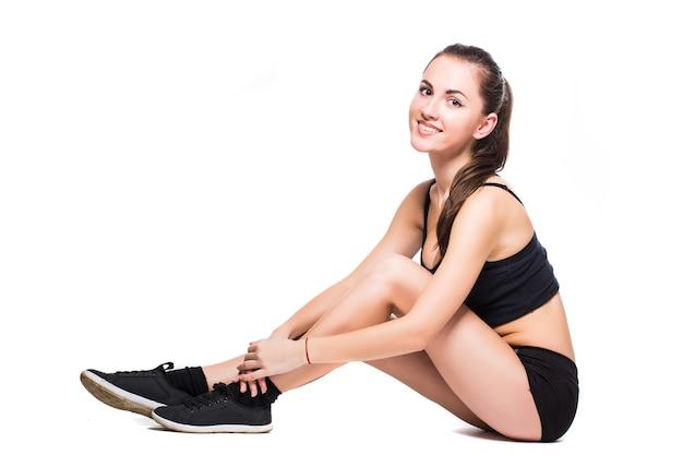 Fitness kobieta robi ćwiczenia rozciągające na białym tle