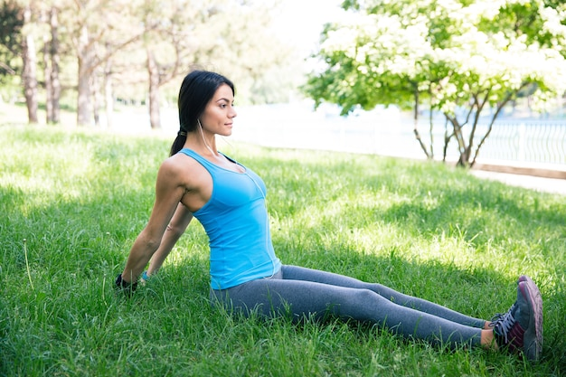 Fitness kobieta robi ćwiczenia rozciągające w parku