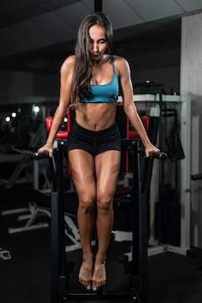 Fitness kobieta robi pompki na nierównych barach w siłowni crossfit.