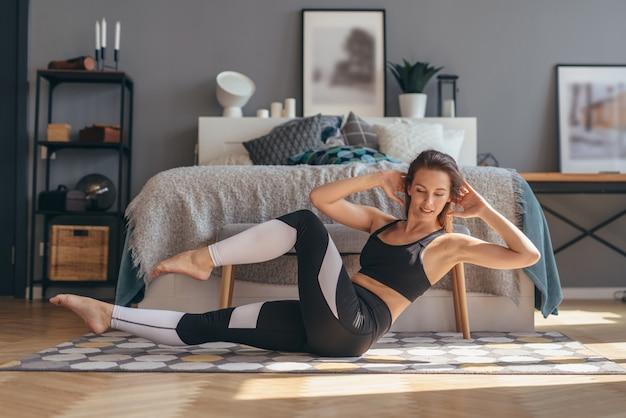 Fitness kobieta robi skręca ćwiczenia. poranny trening w domu.