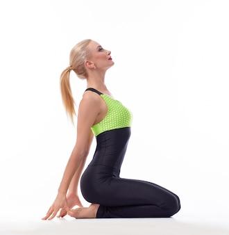 Fitness kobieta siedzi na kolanach, rozciągając plecy