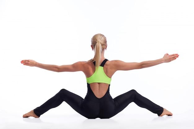 Fitness kobieta siedzi, rozciągając nogi i rozkładając ramiona na białym tle copyspace