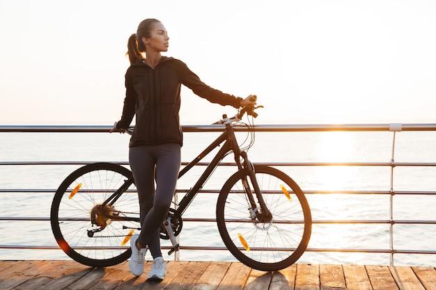 Fitness kobieta stojąca z rowerem na promenadzie, podczas wschodu słońca nad morzem