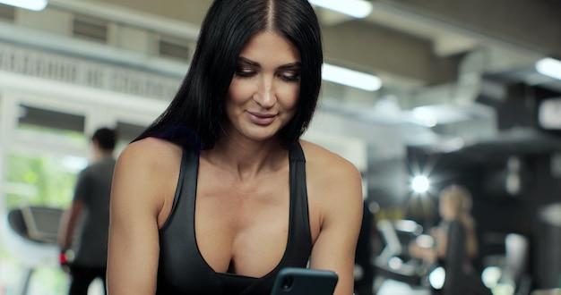 Fitness kobieta trzyma smartphone w klubie sportowym. zbliżenie piękna lekkoatletka sms-y na telefon komórkowy w siłowni. uśmiechnięta sportowa kobieta odpoczynek z telefonem komórkowym.