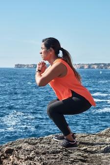 Fitness kobieta w sportowym kompletie treningowym z elastyczną opaską, ciężarami, ćwiczeniami na siłownię, nad wodą.