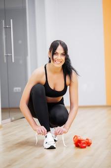 Fitness kobieta wiązanie trampki liny. motyw odzież sportowa i moda